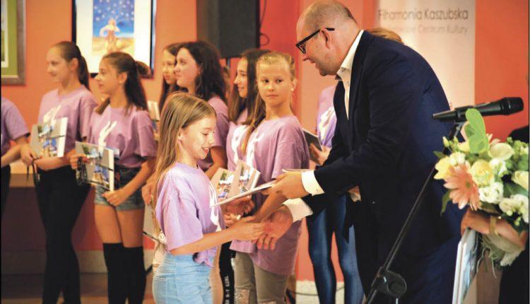 Arkadiusz Kraszkiewicz, zastępca prezydenta Wejherowa gratuluje małym tancerkom sukcesu.