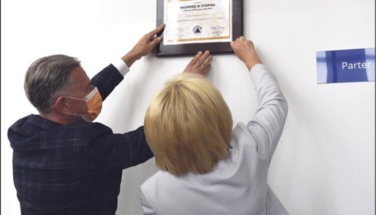 Podczas uroczystości w Powiatowym Zespole Szkół w Redzie, starosta Gabriela Lisius i wykonawca inwestycji Mariusz Gustowski zawieszają tablicę, informującą o nagrodzie.